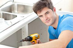 Handsome man with a drill repairing a kitchen sink. Handsome man holding a drill repairing a kitchen sink at home stock image