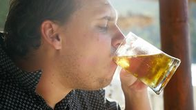 Handsome man is drinking beer in a cafe beach on tropical island. slow motion. 1920x1080. Hd stock video footage