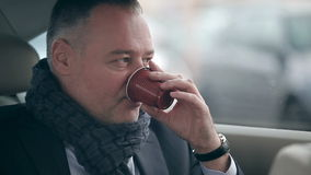 Handsome man drinking coffee in the car stock video