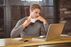 Handsome man drinking coffee and concentrating on laptop Royalty Free Stock Images