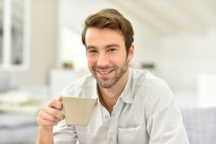 Handsome man drinking coffee at home Stock Photos