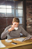 Handsome man drinking coffee and reading newspaper Stock Image