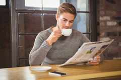 Handsome man drinking coffee and reading newspaper Stock Photos