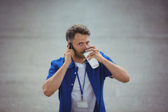 Handsome man drinking coffee while talking on mobile phone Stock Images
