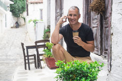 Handsome man drinking coffee and using cellphone. Stock Photo