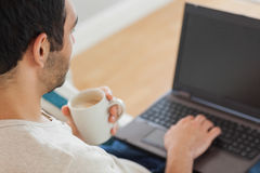 Handsome man drinking coffee while using his laptop Royalty Free Stock Photography
