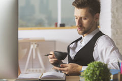 Handsome man drinking coffee at workplace Stock Image