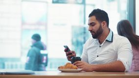 Handsome man drinking a cup of coffee, and smiling towards the phone screen. Everyday routine, social networks. Using stock video footage
