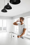 Handsome Man Drinking Glass Of Fresh Water Indoors In Morning Royalty Free Stock Photography