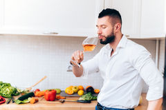 Handsome man drinking a glass of rose wine during dinner preparation. Modern cook sipping from wine while cooking salad Royalty Free Stock Photography