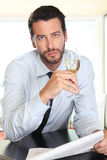 Handsome man drinking a glass of sparkling wine white, sitting at the bar Royalty Free Stock Photos