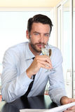 Handsome man drinking a glass of sparkling wine white, sitting a. T the bar with newspaper, portrait Stock Photos
