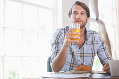 Handsome man drinking orange juice at breakfast. At home in the living room Stock Photography