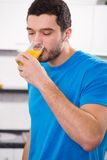 Handsome man drinking orange juice. In the kitchen at home Royalty Free Stock Photography