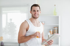 Handsome man drinking orange juice while reading the news. In his kitchen Stock Images