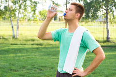 Handsome man drinking water from plastic bottle Royalty Free Stock Photo