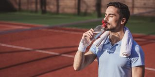 Man playing tennis. Handsome man is drinking water while playing tennis on court outdoors Stock Photography