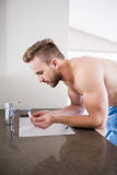 Handsome man drinking water from the sink Stock Images