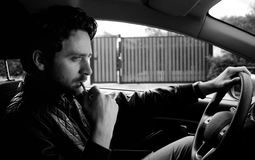 Handsome man driving car smoking cigarette black and white Stock Photo