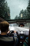 Handsome man driving in car through the winter forest Royalty Free Stock Photos