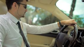Handsome man driving expensive car to work, business class transport service. Stock footage Royalty Free Stock Photography