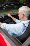 Handsome man driving his red convertible Stock Photography