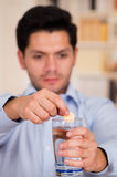Handsome man dropping effervescent tablet in glass of water Stock Image
