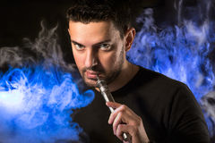 Handsome man with e-cirarette in a vapor Stock Photography