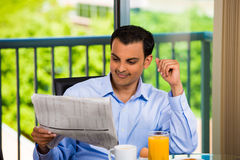 Handsome man eating breakfast and reading newspape royalty free stock images