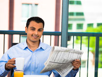 Handsome man eating breakfast and reading newspaper Royalty Free Stock Photo