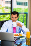 Handsome man eating breakfast and working on laptop Stock Photo