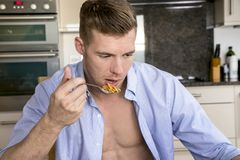 Handsome man eating cereal at breakfast table with open blue shirt revealing defined chest and pecs. Man sitting at breakfast table in kitchen, eating cereal Royalty Free Stock Image