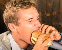 Handsome Man eating Cheeseburger Royalty Free Stock Images
