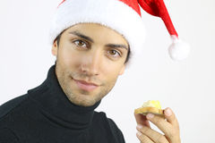 Handsome man eating a foie gras toast. Handsome man with a Santa hat eating a foie gras toast stock photography