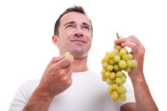 Handsome man eating a green grapes, Stock Photo