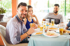 Handsome man eating hamburger with friends Stock Photo