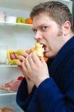 Handsome man eating piece of cake. Near open fridge Stock Image
