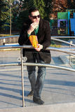 Handsome Man Eating Popcorn Outside in a Park. On a Sunny Winter Day Stock Photo