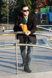 Handsome Man Eating Popcorn Outside in a Park. On a Sunny Winter Day Royalty Free Stock Image