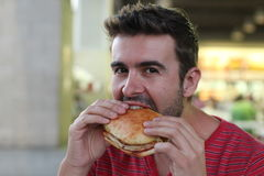 Handsome man eating a sandwich.  Stock Photography