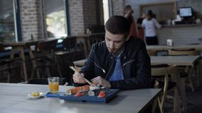 Handsome man eating tasty sushi in cafe 4K.  stock footage