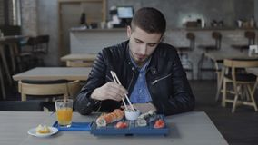 Handsome man eating tasty sushi in cafe 4K.  stock video footage