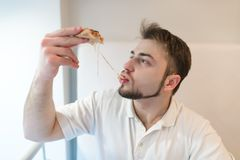 A handsome man eats a hot piece of pizza. The man eats a cheese that stretches out with a slice of pizza. Stock Images