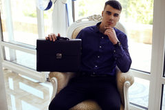 Handsome man in elegant clothes with bags posing in interior Stock Image