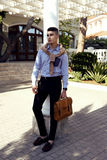 Handsome man in elegant outfit with bag posing outdoor Royalty Free Stock Photography