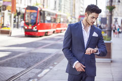 Handsome man elegantly dressed looking at his watch Royalty Free Stock Image