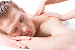 Handsome man enjoying a deep tissue back massage. Royalty Free Stock Images