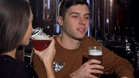 Handsome man enjoying his beer, drinking with his girlfriend at the pub. Young couple drinking delicious craft beer at the bar, celebrating anniversary. Love stock video footage