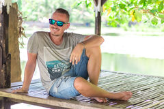 Handsome man enjoying his summer holidays outdoors the tropical Bali island, Indonesia. Portrait of young man in wooden royalty free stock photos