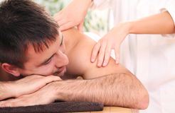 Handsome man enjoying procedure of massage Royalty Free Stock Photos